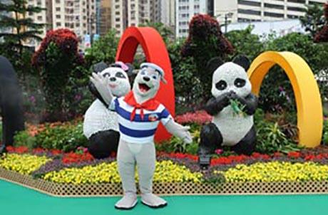 图片说明2: 海洋公园威威狮令为大家介绍由大熊猫盈盈和乐乐、海豚及奥运五色扣环标志构成的花卉作品