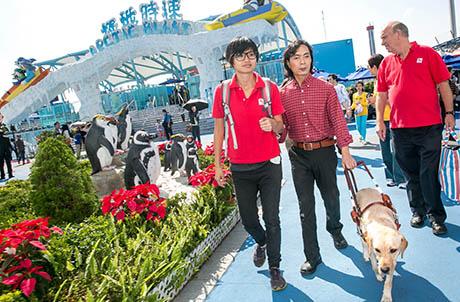 圖3a, 3b, 3c:視障人士黃天朗先生與導盲犬Jolee同遊海洋公園,與不同動物大使相遇,Jolee仍保持一貫專業態度,冷靜為黃先生領路